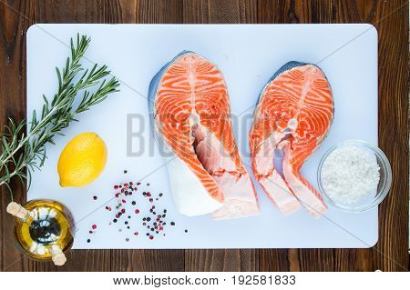 steaks of salmon with a sprigs of rosemary lemon pepper sea salt on a white cutting board on wooden background top view.