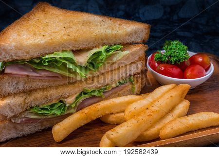Sandwich with ham cheese lamb lettuce simple and French fries on wood plate.