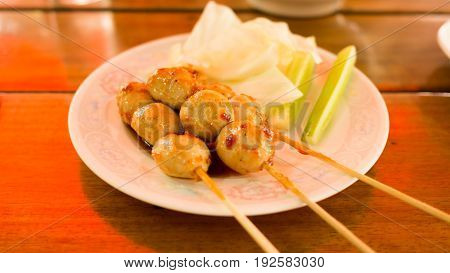 Roasted pork ball pour with sweet spicy sauce and vegetable in white plate on wood table