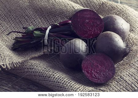 Bunch of beetroot on a brown burlap cloth in an artistic conversion