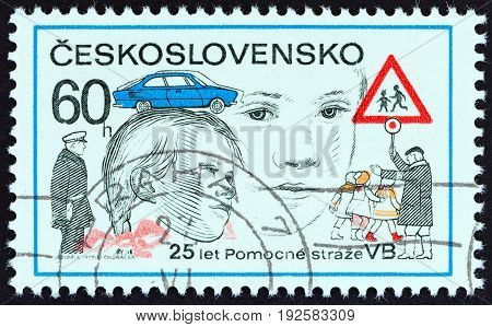 CZECHOSLOVAKIA - CIRCA 1977: A stamp printed in Czechoslovakia issued for the 25th anniversary of Police Aides Corps shows Children Crossing Road, circa 1977.