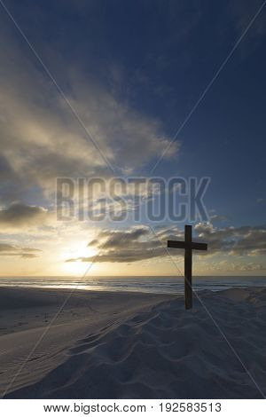 An old cross on a sand dune next to the ocean with a calm sunrise