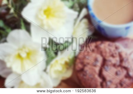 Bouquet of daffodils cup of coffee and chocolate muffin blurred background