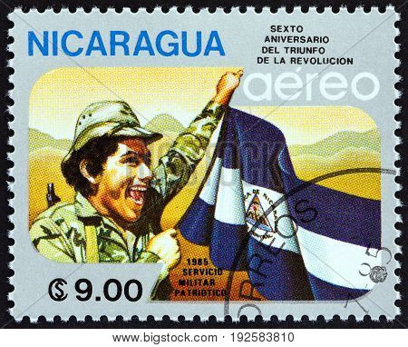 NICARAGUA - CIRCA 1985: A stamp printed in Nicaragua issued for the 6th anniversary of Revolution shows soldier and flag, circa 1985.