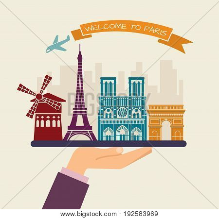 The hand holds the sights of Paris on a tray. The plane and the words welcome to Paris on the ribbon
