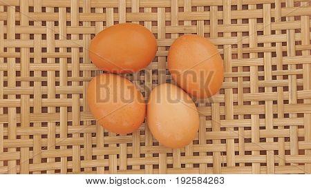 Four chicken eggs on a basketwork background