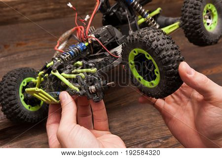 Rc radio control car crawler model repair on wooden background. Green toy suv in repairshop workplace, free space