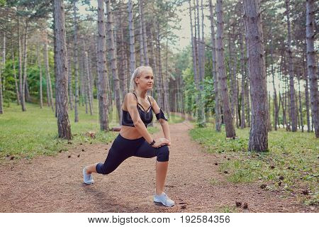 Girl warm up in forest. Young woman  doing warm-up before training in the forest.