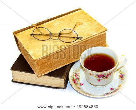 glasses for reading lie on old books in a shabby rumpled cover next to a cup of tea isolated on white