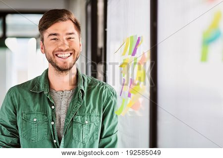 I found a solution. Portrait of excited male worker standing near glass board with colorful stickers. He is looking at camera and smiling. Copy space in right side