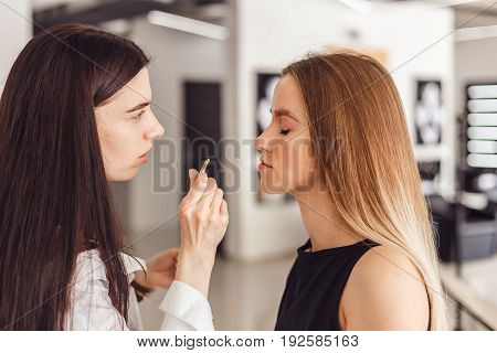 Young woman cosmetologistt weezing eyebrows of model in beauty saloon. Young woman plucking eyebrows with tweezers close up