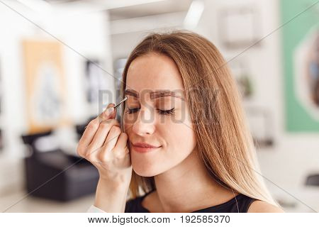 Young woman tweezing her eyebrows in beauty saloon. Young woman plucking eyebrows with tweezers close up