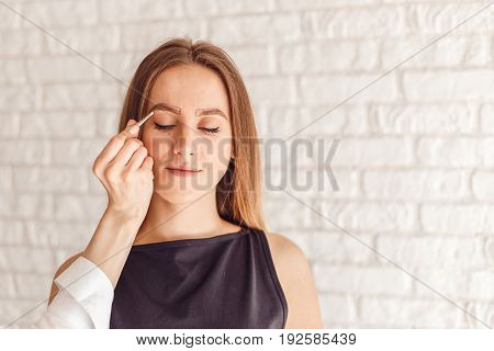 Portrait of a model and the masters hand with tweezers. Young woman tweezing her eyebrows.