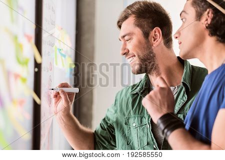 Joyful male worker is drawing diagram on board while discussing project with his colleague. He is smiling with excitement