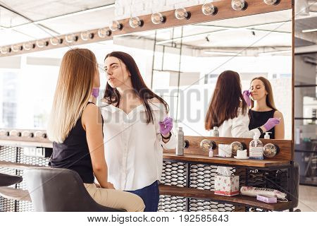 Cosmetologist making a service to the young woman in the salon. The model sits on a chair and can be seen silhouetting in the mirror.