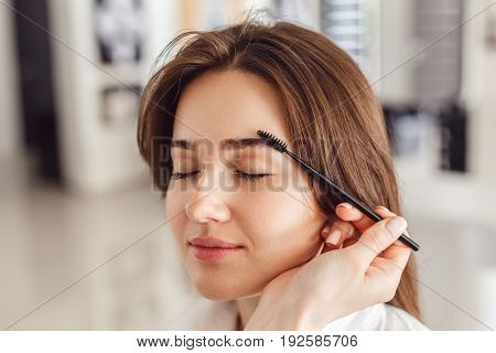 Woman correcting eyebrows form. Closeup beautiful woman with eyebrow brush tool in salon.