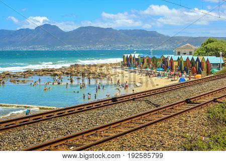 Cape Town, South Africa - January 10, 2014: the blu flag Muizenberg Beach in Cape Town located in the Indian Ocean, crowded on weekends, with its famous colorful Victorian bathing boxes.