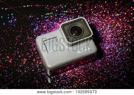 Kharkov, Ukraine - April 13, 2017: GoPro HERO 5 digital action camera in flashlight with sparkles on black. Compact gadget waterproof , support 4k video and is often used in extreme photography