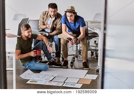 Joyful young start-up team is observing graphics on papers. Man is sitting on floor and smiling while drinking cup of coffee