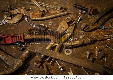 Selection of old worn well used tools on top of an old wooden workbench.