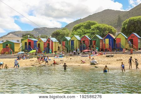 Cape Town, South Africa - January 10, 2014: the popular retro Muizenberg Beach in Cape Town, Indian Ocean, with its famous colorful Victorian bathing boxes.