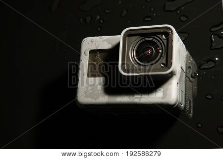 Kharkov, Ukraine - April 13, 2017: GoPro HERO 5 digital action camera with water drops top view on black. Compact gadget waterproof , support 4k video and is often used in extreme photography