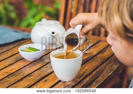 Happy Nice Boy Pours Honey Into The Tea In Summer Green Garden. Portrait. Outdoor
