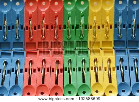 colorful plastic clothes peg clipping hard white paper