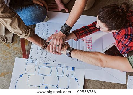 Team spirit. Happy young men and woman and holding hands together under papers with graphics on floor. Top view