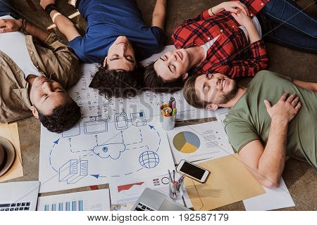 Satisfied with teamwork. Tired young men and woman are relaxing on floor near various business graphics. Their eyes are closed with pleasure