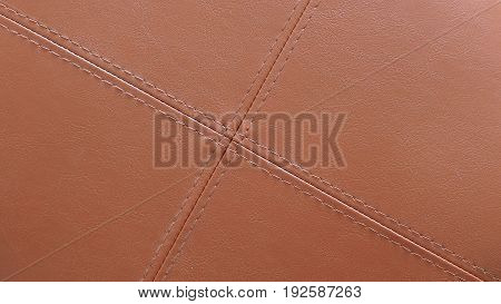 Texture of brown leather with light brown stitching in cross pattern. Useful for background design