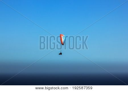 Paragliding over Table Mountain National Park in Cape Town, Western Cape, South Africa in the blue sky.