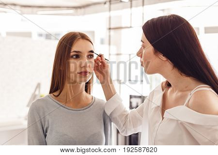 Master makeup corrects, and gives shape for eyebrows in a beauty salon. Professional care for face.