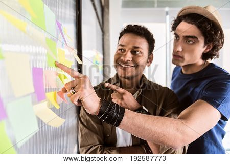 This is the great idea. Thoughtful young man is pointing finger at sticker on glass board. His colleague is looking there and smiling. Focus on male hand