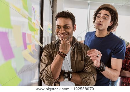 Business decision. Clever young men are discussing near project while reading information on stickers. They are standing and smiling. Portrait