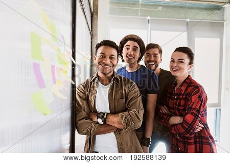 Many men, many minds. Waist up portrait of happy start-up team standing near glass wall with colored stickers. They are looking at camera and laughing