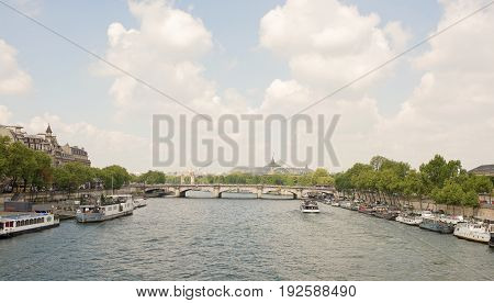 ParisFrance- April 29 2017: To the Concord Bridge the ship sails with tourists. On the embankments there are ships. People walk along the embankments