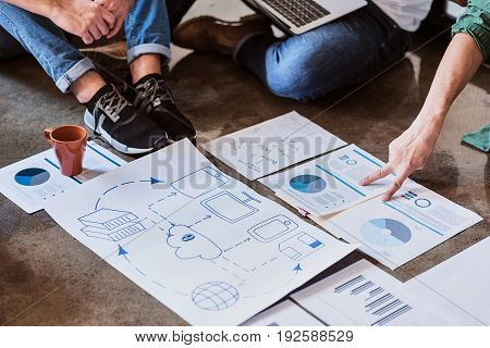 Close up of internet cloud connection drawing on floor. Male hand is pointing finger at graphic while explaining idea to colleagues