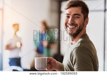 Waist up portrait of joyful young man making coffee break in office. He is holding mug and laughing