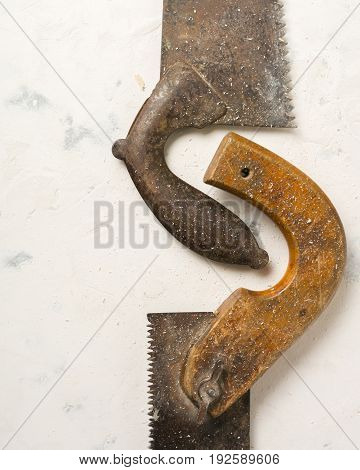 Large Teeth Of An Old Saw On Wood. Sharp And Uneven Edges. Rusted Surface. Light Stone Background.