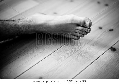 Close Up On Male Foot Over Wooden Floor