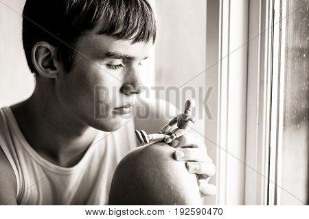 Serious Teen Boy Looking At Wooden Manikin