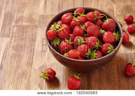 Fresh red strawberries in a brown clay bowl on wooden table. Many strawberries in the bowl and several strawberries on the table. Food backgrounds and still-life. Horizontal photo. Tasty, useful and natural product. Concept of the vitamin food.