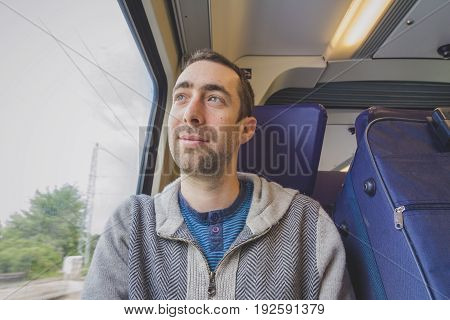 Young Man Traveling On A Train And Looks Out The Window And Smiling