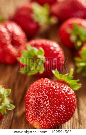 Close-up of the fresh red strawberries on wooden table. Appetite big strawberries. Vertical photo. Food backgrounds and still-life. Tasty, useful and natural product. Concept of the vitamin food.