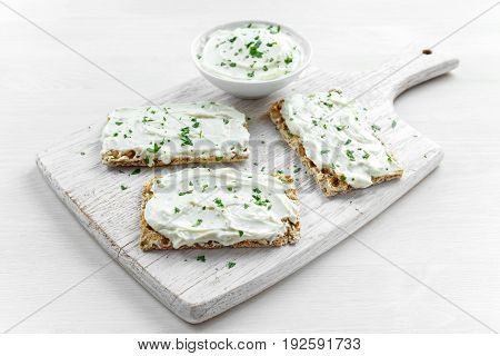 Homemade Crispbread toast with Cream Cheese and parsley on white wooden board background