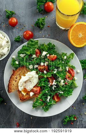 Breakfast Green Kale with poached eggs, feta cheese, tomatoes and toast. healthy food.