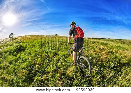 Young cyclist riding mountain bicycle through green meadow against beautiful sky. Attractive sportsman in the black sportwear, with helmet and backpack. Fisheye. Concept of the healthy and active lifestyle.