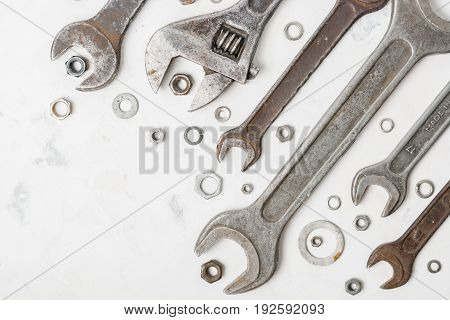 A Lot Of Old Wrenchs On A Light Stone Background. Nuts And Washers Of Different Sizes.