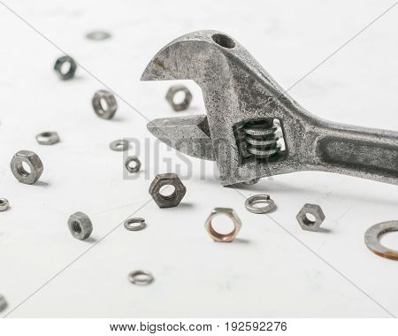 Wrench On A Light Stone Background. Nuts And Washers Of Different Sizes.